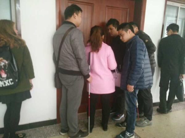 2月15日下午2时50分,雨花区法院第六审判厅门口,原告小石的朋友们在厅外关注着厅内的情况。 澎湃新闻记者 谭君 实习生 陆慧辉 图