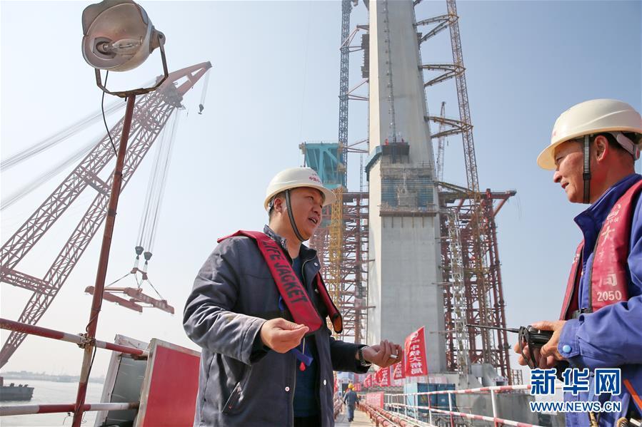 11月9日,顾惠明(左)在沪通长江大桥29号南主塔施工工地和同事交流。新华社发(许丛军)