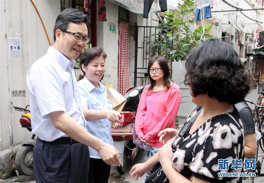 邹碧华(左一)在社区走访时与群多交流(2013年9月29日摄)。 新华社发