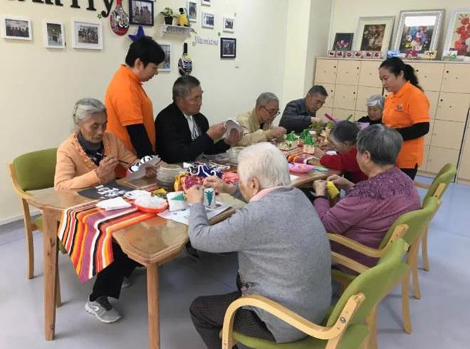 2018年11月6日,8位年龄在79至92岁的老人正在做手工。习近平与他们一一握了手。来源:央视新闻