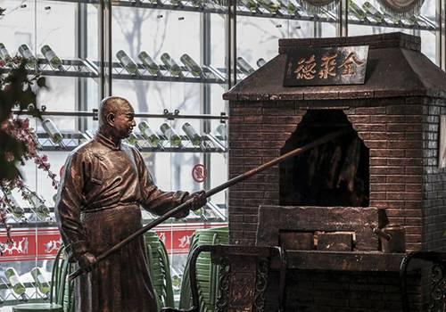 """人才流失上面说了,其实烤鸭工艺也不复从前。有些烤鸭店还打着""""果木挂炉""""的招牌,但实际上,因为环保要求,现在中国的烤鸭行业基本都是电烤炉自动烤制。"""