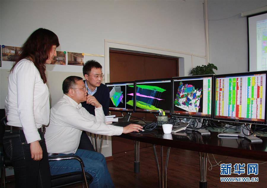 黄大年(中)带领科研团队成员研究问题(2010年11月22日摄)。新华社发