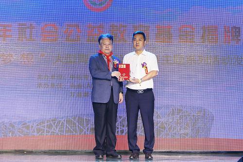赵蓬奇(左)为爱心企业代表(右)颁发荣誉证书