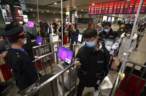 2月2日,旅客在北京西站出站口通过红外测温仪。-中新社